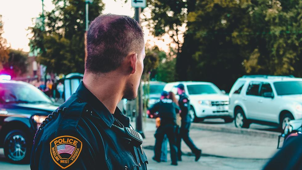 Police officer turning his head toward a scene of two other police officers arresting a seemingly young person.
