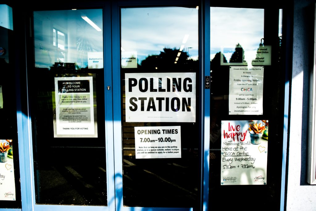 sign for polling station posted on a glass door